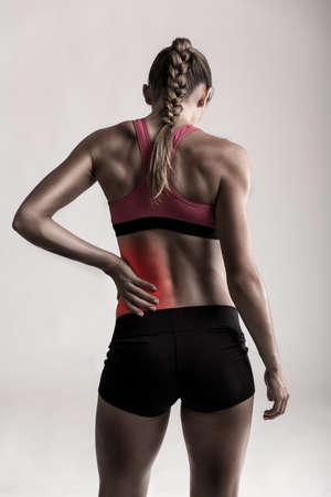 Studio shot of a sporty young woman holding her lower back in pain Archivio Fotografico
