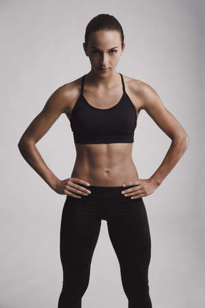 Portrait of sporty young woman with muscular body looking at camera Stock Photo