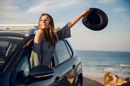 Beautiful woman looking out the car window waving with a hat, near the beach