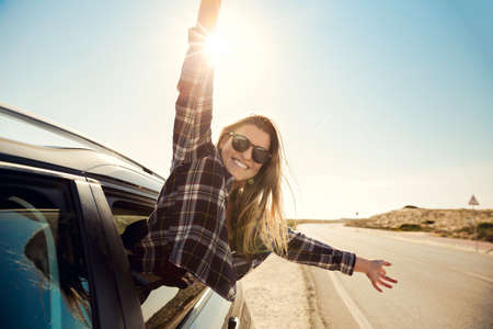 Beautiful woman looking out the car window with open arms enjoying the sunshine Standard-Bild