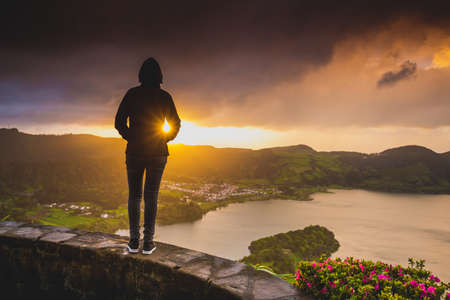 Back view of a woman looking to a beautiful sunset in Açores, Portugal Stock Photo
