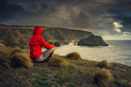 Woman sitting and looking to the sea, Azores, Portugal