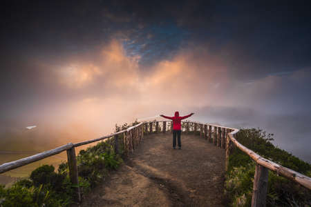 Woman standing on a beautiful path with arms open at the sunset Reklamní fotografie