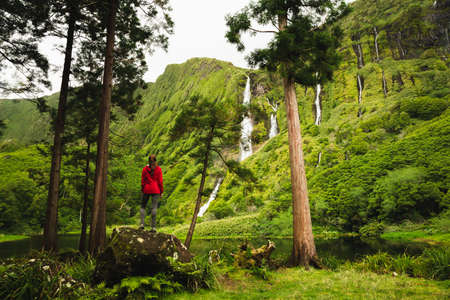 Woman standing over a stone enjoying the beautiful waterfalls from Azores, Portugal