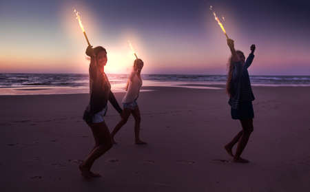Best friends running on the beach celebrating the summer with fireworks
