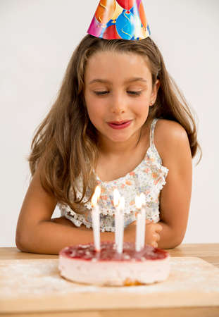 Shot of a young girl blowing out the candles on her birthday cake