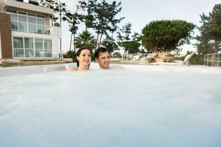 Young couple in a luxury hotel inside a jacuzzi in a rainy day  Stok Fotoğraf