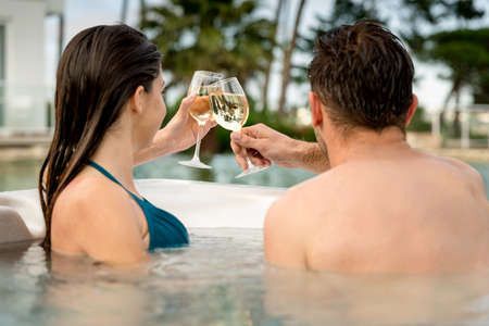 Young couple inside a jacuzzi and toasting  Stok Fotoğraf