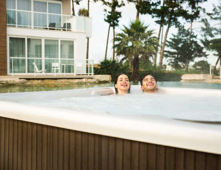Young couple in a luxury hotel inside a jacuzzi in a rainy day  Фото со стока