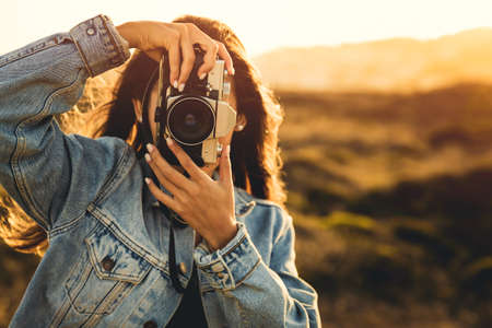Beautiful woman taking picture outdoors with a analog camera
