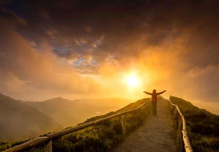 Frau, die auf einem schönen Weg mit den Armen offen am Sonnenuntergang steht