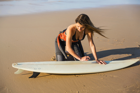 Two beautiful surfer girls at the beach getting ready for surfing Stock Photo