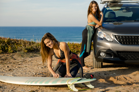 Two beautiful surfer girls near the coastline with her car, and getting ready for surfing Stock Photo