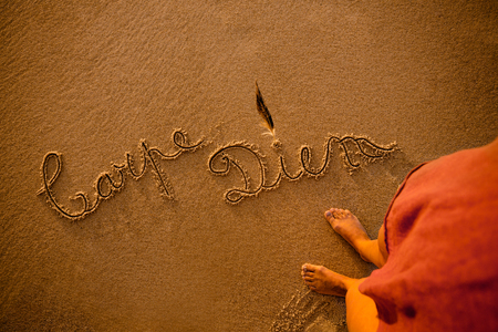 Woman on the beach with the words Carpe Diem written in the sand Stok Fotoğraf - 115985371