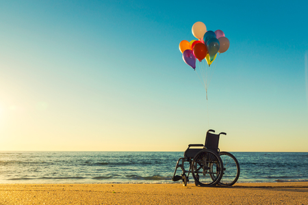 Wellchair on a beach with colored  ballons