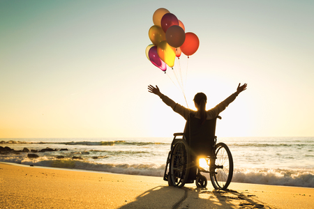 Hombre discapacitado en silla de ruedas con globos de colores en la playa