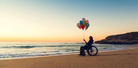 Mujer discapacitada en silla de ruedas con globos de colores en la playa
