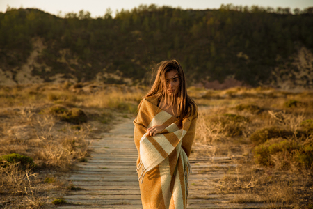 Beautiful young woman walking over a wood path wrapped with a wool towel