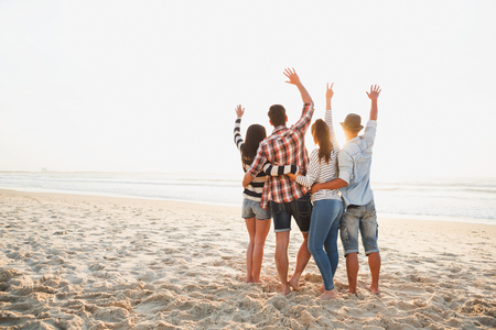 Group of friends at the beach and enjoying the sunset