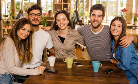 A group of friends looking to the camera and drinking coffee at the cafe Reklamní fotografie