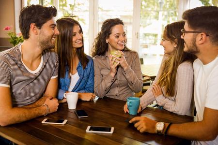Eine Gruppe von Freunden, die im Café reden und Kaffee trinken