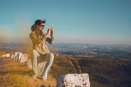 Woman taking  a picture with a cellphone to the beautiful landscape