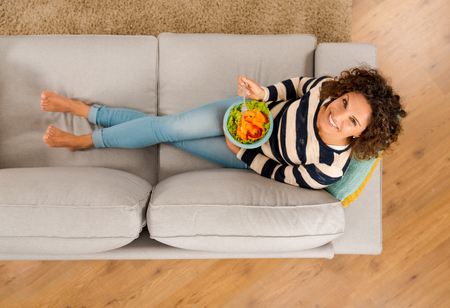 Top view of a beautiful woman on the sofa eating a healthy salade Фото со стока