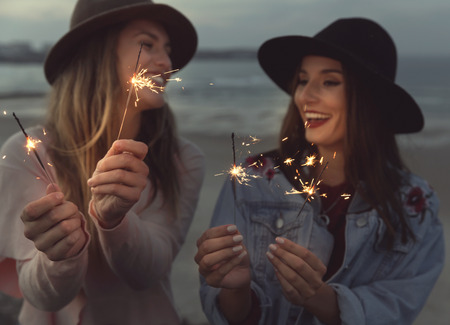 Two best friends celebrating, holding sparklers at beach Фото со стока