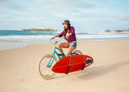 Beautiful surfer girl riding her bicycle on the beach with a surfboard