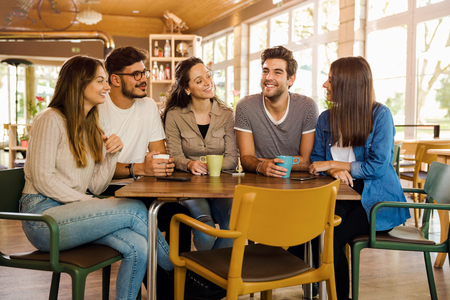 A group of friends talking and drinking coffee at the cafe Stockfoto