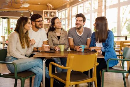 Un grupo de amigos hablando y tomando café en la cafetería. Foto de archivo