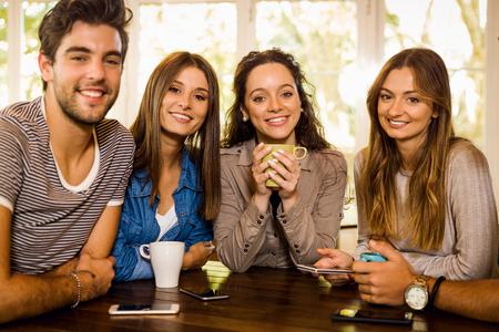 Un grupo de amigos mirando a la cámara y tomando café en la cafetería.