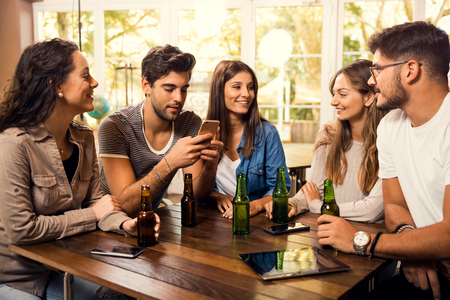 A group of friends at the bar drinking a beer Imagens