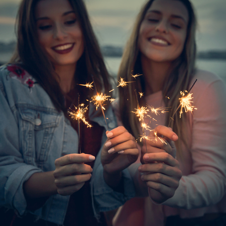 Two best friends celebrating, holding sparklers at beach Imagens