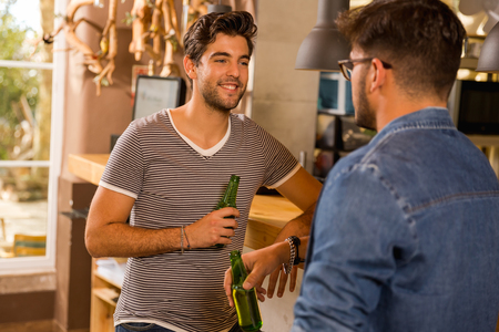 Two friends having a drink at the pub Imagens