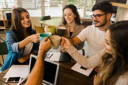 Group of friends studying together and making a toast with coffee Imagens