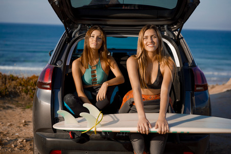 Two beautiful and sexy surfer girls sitting on the trunk of car holding a surfboard