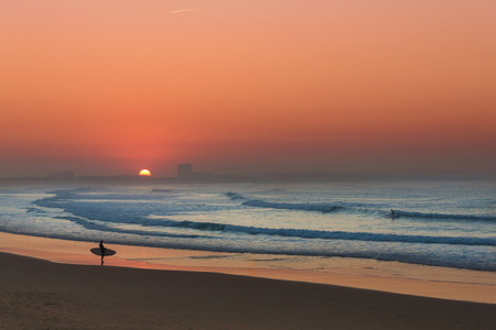 Surfer at sunset checking the waves