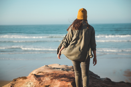 Woman with a yellow cap and walking over a cliff to see the beach