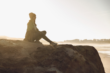 Beautiful woman sitting on a cliff over the beach Imagens