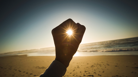 Female hand holding the sun on a signal of hope and strength