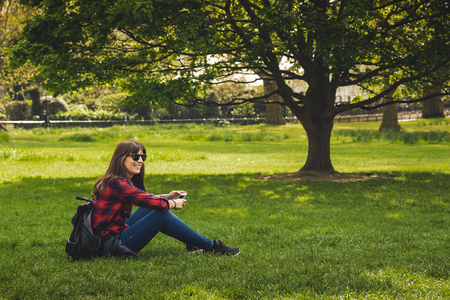 Beautiful woman sitting on the grass and relaxing Imagens