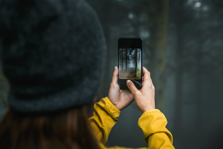 Female traveler taking a picture to a forest with her cellphone Imagens - 130027616