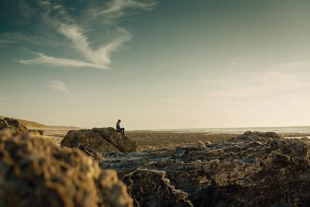 Beuutoful woman alone in the beach sitting on the rocks