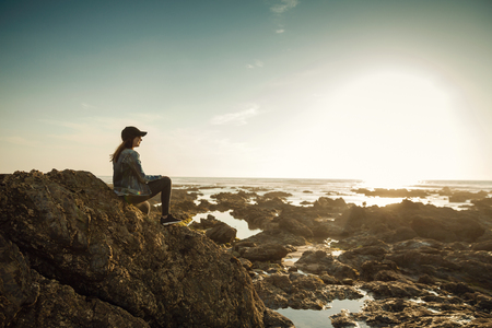 Beautiful woman alone in the beach sitting on the rocks Imagens