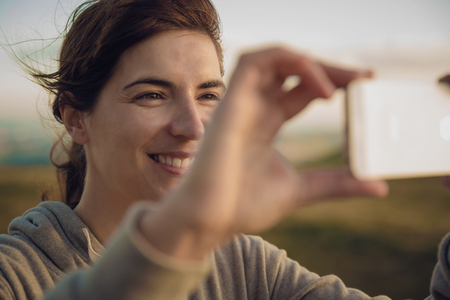 Woman in nature taking a picture with a cellphone