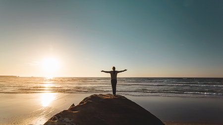 Woman on the top of a clif looking to the ocean with arms raised