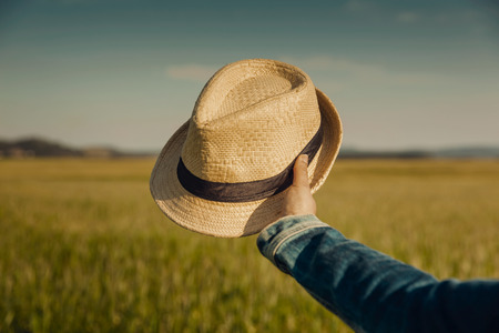 Female hand holding  a straw hat