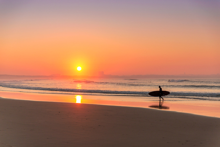 Surfer leaving the ocean after a long day of surf( Imagens
