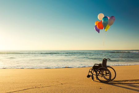 Wheelchair on a beach with colored  ballons